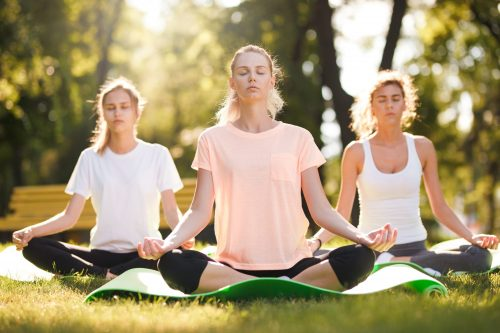Group of young women practicing yoga, morning meditation in nature at the park.