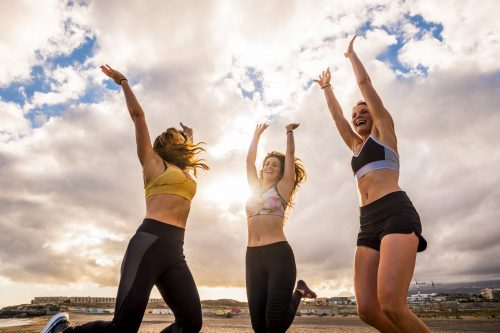 Happy group of females atlethes jumping for win victory concept and success competition together like a team - joyful for beautiful caucasian people having fun together