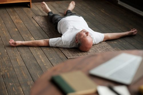 Senior caucasian man meditating on a wooden floor of living room and lying in Shavasana pose after practice. Yoga relax, meditating concept, close up