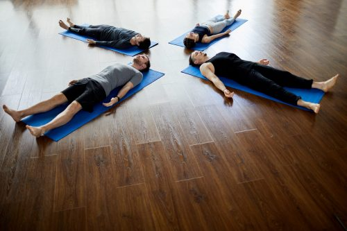 Group of relaxed young people lying on mats in circle and doing savasana while napping at end of yoga practice