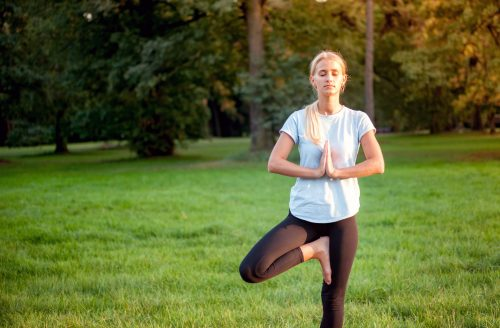 Yoga in the park, young woman doing tree pose vrksasana