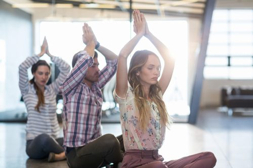 Business people performing yoga on floor in office